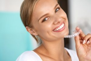 Woman holding Invisalign.