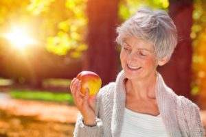 Woman with dentures in Pittsburg holding an apple and smiling