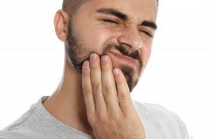 Bearded man in gray shirt rubbing his jaw