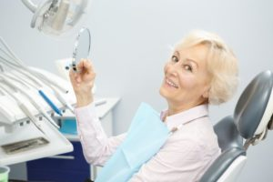 Woman with dental implants in Pittsburgh smiles while visiting her dentist
